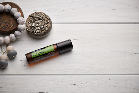 doTERRA Forgive Touch blend, jewellery and trinkets on white rustic wooden background.