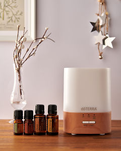 doTERRA Lumo diffuser with Cardamom, Cinnamon, Clove and Wild Orange essential oils and holiday decorations on a side table.
