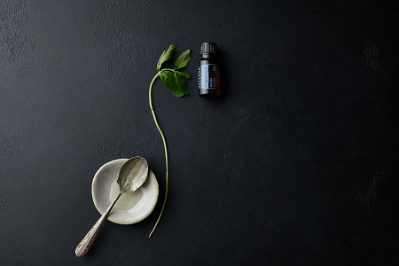 doTERRA Peppermint with a bowl, spoon and a peppermint branch on a black stone background.