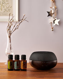 doTERRA Brevi Walnut diffuser with Bergamot, Spearmint and Tangerine essential oils and holiday decorations on a side table.