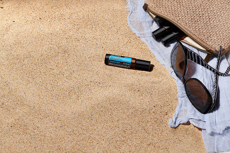doTERRA Breathe Touch with sunglasses, scarf and roller bottles in a clutch on the beach.
