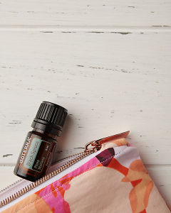 doTERRA Black Spruce and essential oil bag on a white wooden background.