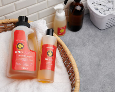 doTERRA On Guard Laundry Detergent and On Guard Cleaner Concentrate in a basket of white fluffy towels on a laundry bench.