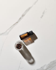 doTERRA Clove essential oil and cloves in a bottle on white marble in sunlight.
