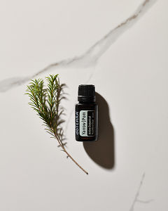 doTERRA Yarrow Pom essential oil blend and a plant stem in direct sunlight on a white marble background.