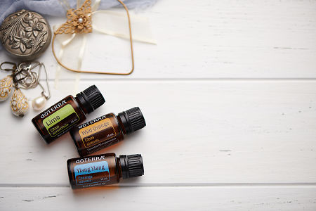 doTERRA Lime, Wild Orange and Ylang Ylang oils with romantic jewellery on a white vintage wooden background.