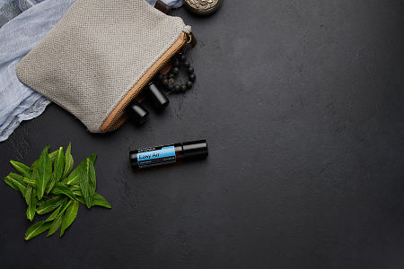 doTERRA Easy Air Touch with clutch, accessories and mint leaves on a black concrete background.