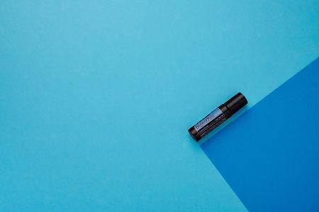 doTERRA DigestZen Touch on a dark blue and light blue geometric background.