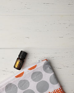 doTERRA Arise and an essential oil bag on a white wooden background.