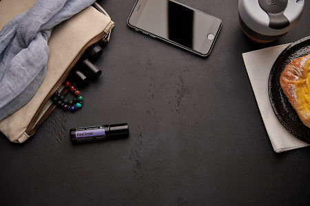 doTERRA PastTense with a leather clutch, roller bottles, cell phone, coffee and food on a black background.