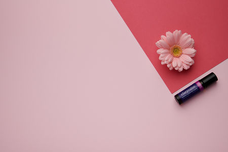 doTERRA ClaryCalm with a flower on a dark and light geometric background.