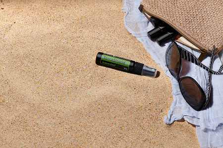 doTERRA TerraShield spray with sunglasses, scarf and roller bottles in a clutch on the beach.