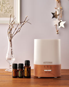 doTERRA Lumo diffuser with Motivate, Douglas Fir and Citrus Bliss essential oils and holiday decorations on a side table.