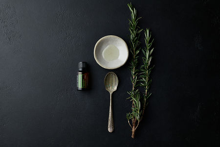 doTERRA Rosemary with a vintage spoon, rustic bowl and a rosemary branch on a black stone background.