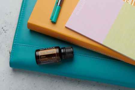 doTERRA Wild Orange oil with business folder, planner, pen and to do list on white concrete background.