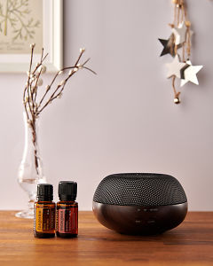 doTERRA Brevi Walnut diffuser with Tangerine and Wintergreen essential oils and holiday decorations on a side table.