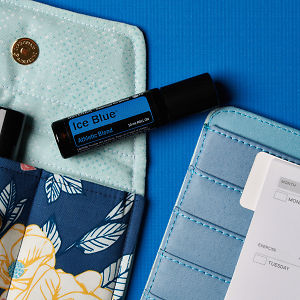 doTERRA Ice Blue Roll On on an essential oil bag with a diary on a blue textured background.