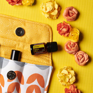 doTERRA Cheer on an essential oil bag with scattered flowers on a yellow textured background.