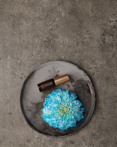 doTERRA Blue Lotus Touch 4ml on a ceramic plate with a blue flower on a gray stone background.