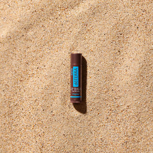 doTERRA Spa Original Lip Balm in direct sunlight on the beach.