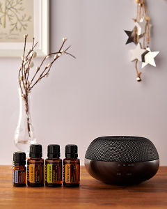 doTERRA Brevi Walnut diffuser with Juniper Berry, Citrus Bliss, Lemongrass and Wild Orange essential oils and holiday decorations on a side table.