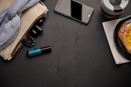 doTERRA Breathe Touch with a leather clutch, roller bottles, cell phone, coffee and food on a black background.