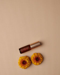 doTERRA Neroli Touch 4ml and a blue flower on a tan linen textured background.