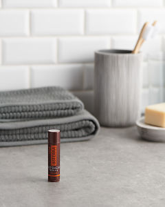 doTERRA Spa Tropical Lip Balm with bathroom acessories on a bathroom bench top.