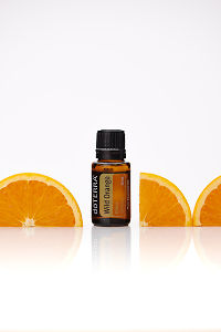 doTERRA Wild Orange with orange slices on a white background with reflection.