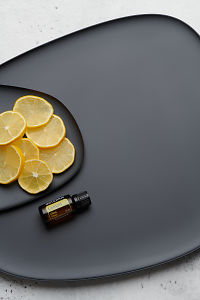 doTERRA Lemon oil and lemon slices on black melamine plate with white concrete background.