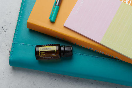 doTERRA Lemon oil with business folder, planner, pen and to do list on white concrete background.