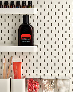 doTERRA On Guard Mouthwash on a bathroom shelf with bathroom accessories and additional doTERRA products.