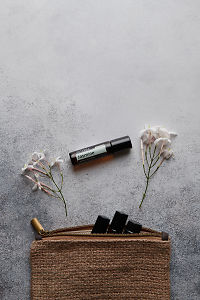 doTERRA Jasmine Touch with jasmine flowers and a clutch filled with roller bottles on a white concrete background.