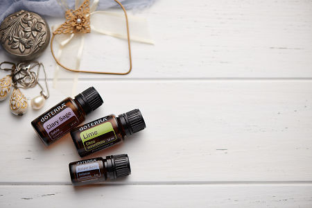 doTERRA Clary Sage, Lime and Juniper Berry oils with romantic jewellery on a white vintage wooden background.