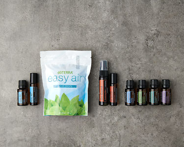 doTERRA Seasonal Essentials Wellness Box Starter Pack on a gray stone background.