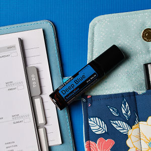 doTERRA Deep Blue Touch on an essential oil bag with a diary on a blue textured background.