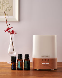 doTERRA Lumo diffuser with Ice Blue, AromaTouch and Balance essential oils on a side table.