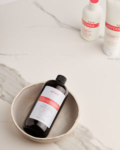 doTERRA Citrus Bloom Foaming Hand Wash in a ceramic bowl with other Citrus Bloom products in the background on a white marble background.