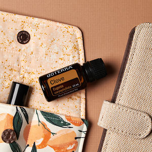 doTERRA Clove on an essential oil bag with a diary on a brown textured background.