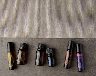 doTERRA Helichrysum Touch, Vetiver, Copaiba, Ice Blue, Neroli Touch and ClaryCalm on a gray stone background.