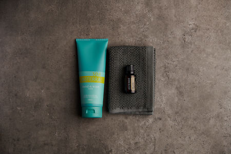 doTERRA Spa Hand and Body Lotion with Myrrh essential oil on a gray washcloth on a stone background.