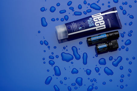 doTERRA Deep Blue Rub, Deep Blue Roll On and Deep Blue 5ml on blue perspex with water drops.