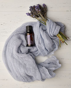 doTERRA Serenity with lavender flowers wrapped in blue material on a white wooden background.
