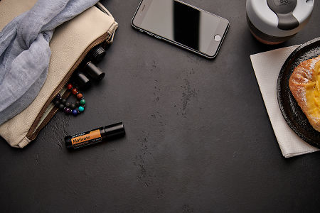 doTERRA Motivate Touch with a leather clutch, roller bottles, cell phone, coffee and food on a black background.