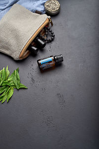doTERRA Breathe with clutch, accessories and mint leaves on a black concrete background.