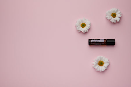 doTERRA Magnolia Touch with white flowers on a pale pink card stock background.