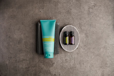 doTERRA Spa Hand and Body Lotion with Bergamot and Lavender essential oil with bathroom accessories on a stone background.