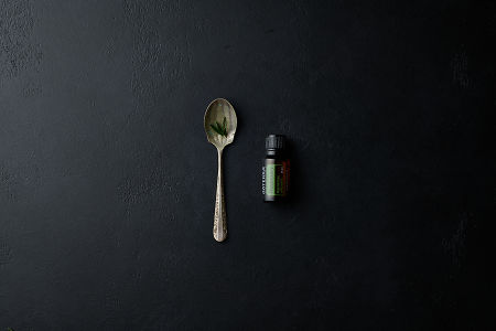 doTERRA Rosemary with a rosemary leaf in a vintage spoon on a black stone background.
