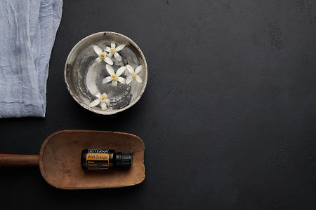 doTERRA Wild Orange in a wooden scoop with orange blosson flowers in a bowl of water on a black concrete backgrouns.