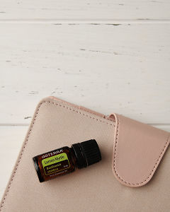 doTERRA Lemon Myrtle with a pink planner on a white wooden background.